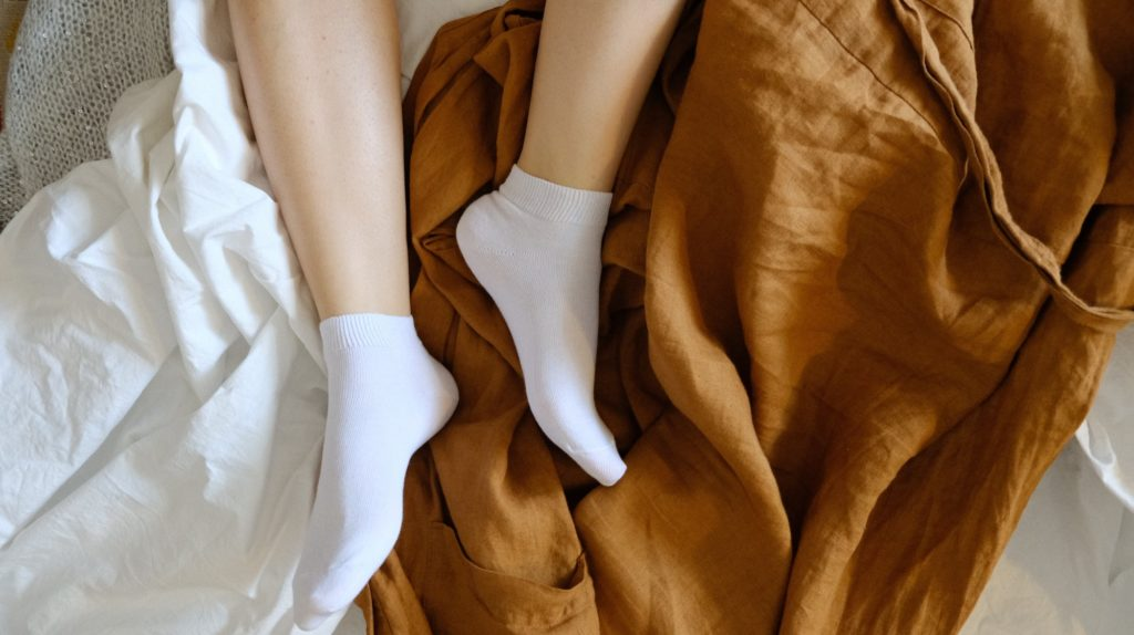 A pair of feet with plain white socks on in bed.