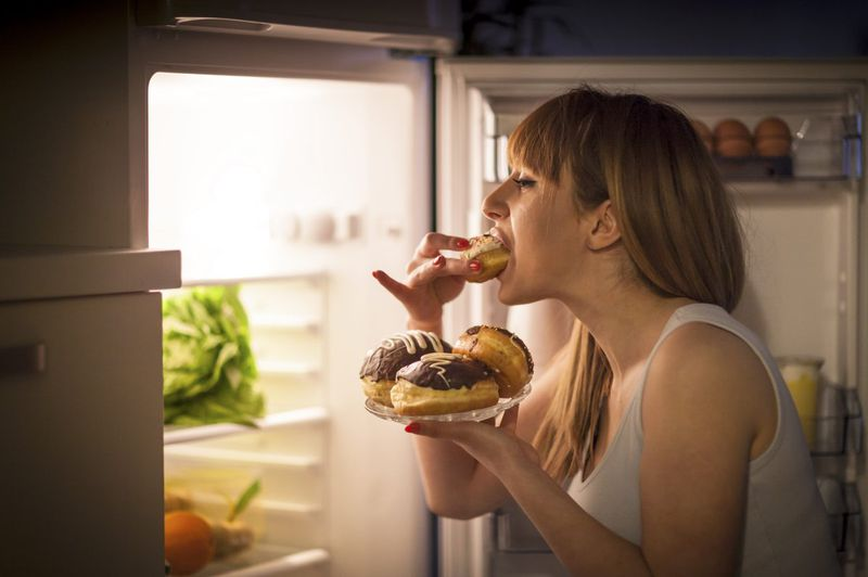 A woman stands in front of her open refrigerator eating a doughnut while holding a plate of other similar doughnuts.
