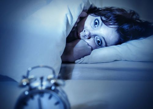 A woman lies in bed at night, wide awake and staring at her alarm clock because she cannot fall asleep.