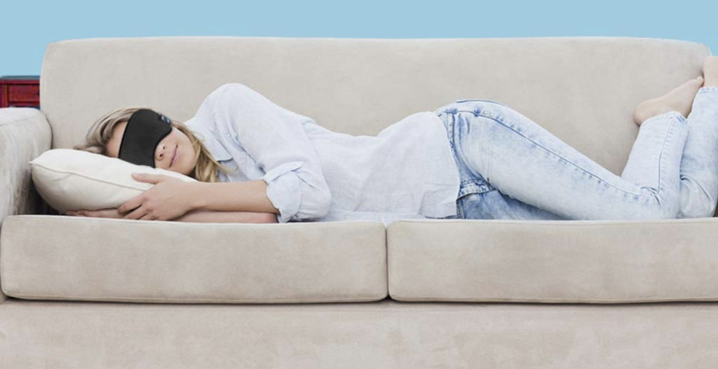 A woman naps on a couch while wearing an eye mask.